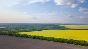 Panoramic view of a field and a village in the distance against a blue sky. Photo from the drone. Panoramic view of fields with rapeseed and cultivated fields, a stock photography