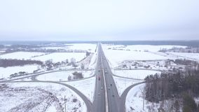 Panoramic view from flying drone car traffic on winter highway. Car driving in highway intersection on background winter landscape stock video footage