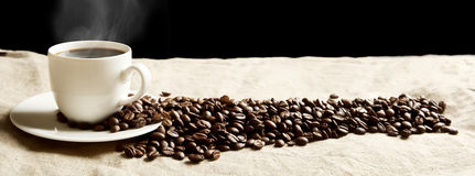 Panoramic view of frothy coffee cup with beans on fabric flax. Closeup scattered coffee cup with foam and plenty beans in panoramic view on fabric linen Stock Photography