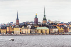 Panoramic view of Gamla Stan old town from the sea with floating boat. Royalty Free Stock Photography