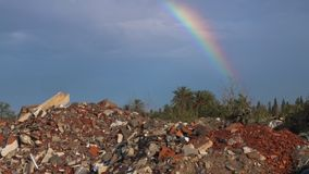 Pollution concept with garbage dump and beautiful rainbow in blue sky. Panoramic view from garbage dump to beautiful rainbow in blue sky. Pollution concept stock footage
