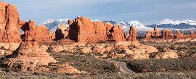 Garden of Eden with Scenic Road winding through vast Monoliths and Arches. Panoramic view of Garden of Eden with the Snow Capped La Sal Mountain Range in the royalty free stock image