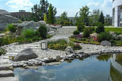 View out the pond to scenery style rock garden. Panoramic view of the garden. Example of decorating and grouping plants Royalty Free Stock Images