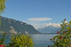 Panoramic view on Geneva Lake. Mountains, hills, greenery and blue sky. Switzerland royalty free stock image