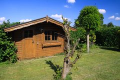 Panoramic view on german garden with green lawn, plane tree, beech hedge and old wooden hut against blue sky stock images