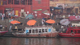 Panoramic view of ghats with people and boats passing at Ganges river. VARANASI, INDIA - 26 FEBRUARY 2015: Panoramic view of ghats with people and boats passing stock footage