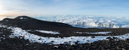 Panoramic view of a glacier sitting above the clouds at the summit of Mount Kilimanjaro taken at sunrise stock images