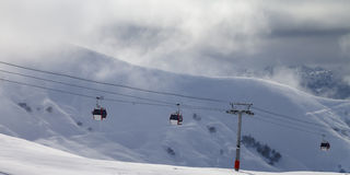 Panoramic view on gondola lifts and off-piste slope in mist Royalty Free Stock Photography