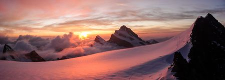 Panoramic view of gorgeous pink sunrise over glacier and high mountain peaks in the Alps Royalty Free Stock Images