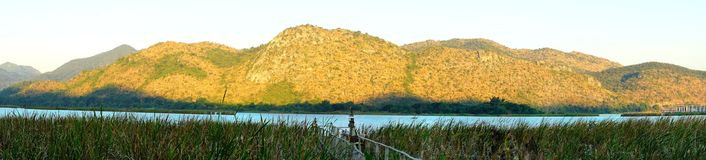 Panoramic view for grass, lake and wood bridge in front of mountain range at Kanchanaburi in Thailand. stock images