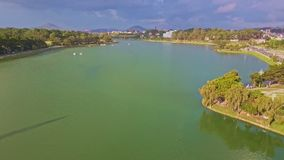 Panoramic view green lake with trees reflected in water. Aerial view large peaceful flat green lake with trees reflected in water at road against city and far stock footage