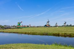 Panoramic view of green meadow with windmills in Zaanse Schans, Netherlands royalty free stock image