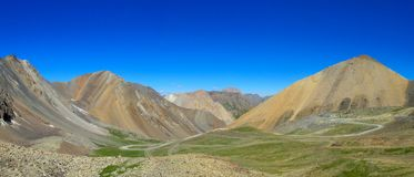 Panoramic view of green mountain valley and serpentine road. In Kazakhstan and Kyrgyzstan. South Inilchek, Enilchek Khan Tengri and Pobeda base camp Stock Images