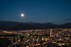 Panoramic view of Grenoble at night with the full moon in the sky and the Belledonne massif in the background stock photography