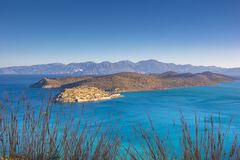 View of the island of Spinalonga with calm sea. Here were  lepers, humans with the Hansen`s desease, gulf of Elounda. Panoramic view of the gulf of Elounda with Royalty Free Stock Photos