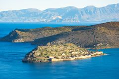 View of the island of Spinalonga with calm sea. Here were  lepers, humans with the Hansen`s desease, gulf of Elounda. Panoramic view of the gulf of Elounda with Royalty Free Stock Photo