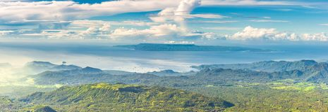 Panoramic view from a high green hill to the sea, islands, rice terraces, fields and forests in indonesia, Agung volcano slope. Panoramic view from a high green stock photography