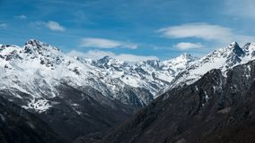 Panoramic view of high mountain peaks and snowcapped ridges at high altitude in the Alps.  Stock Photography