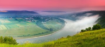 Panoramic view from the hill on bend of the river. Beautiful summer landscape. Colorful pink sky of the morning. royalty free stock photos