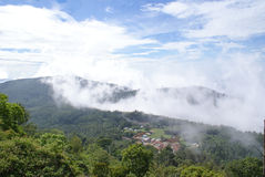 Panoramic view of hill ranges with mist. Panoramic view of a hills covered by green forest and mist with houses at the foot hill Stock Photography
