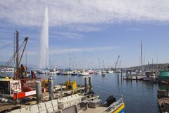 Panoramic view of historic Geneva skyline with famous Jet od`Eau fountain and ships at harbor district in beautiful. Evening light at sunset with blue sky and royalty free stock photo