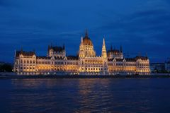 Panoramic view of the Hungarian parliament with illumination of walls from Danube at night. The parliament is a hallmark of Hungary and as it is called by royalty free stock image