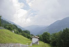 Panoramic view of idyllic alpine mountain scenery with italian house and fresh green meadows in beautiful cloudy weather. In summer, Italy Stock Images