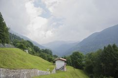 Panoramic view of idyllic alpine mountain scenery with italian house and fresh green meadows in beautiful cloudy weather stock image