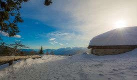 Panoramic view of idyllic winter wonderland with mountain tops and traditional mountain chalet in the Dolomites Royalty Free Stock Photography