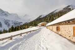 Panoramic view of idyllic winter wonderland with mountain tops and traditional mountain chalet in the Dolomites Stock Photography