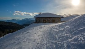 Panoramic view of idyllic winter wonderland with mountain tops and traditional mountain chalet in the Dolomites Stock Photo