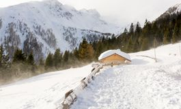 Panoramic view of idyllic winter wonderland with mountain tops and traditional mountain chalet in the Dolomites Royalty Free Stock Photo