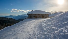 Panoramic view of idyllic winter wonderland with mountain tops and traditional mountain chalet in the Dolomites Stock Images