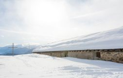 Panoramic view of idyllic winter wonderland with mountain tops and traditional mountain chalet in the Dolomites Royalty Free Stock Images