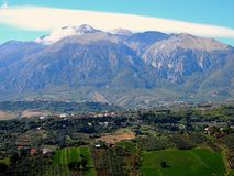 Panoramic view of an imposing mountain with its cultivated lands. Meadows and olive trees at its feet on an autumn day with the blue sky and a playful cloud Royalty Free Stock Image