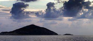 Island in sea and sky with dark clouds at sunset Stock Image