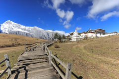Panoramic view of the Jade Dragon Snow Mountain in Yunnan, China and Tibetan Monastery Royalty Free Stock Image