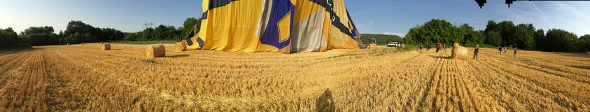 Panoramic view of a just landed ballon in wheat fields Royalty Free Stock Photos