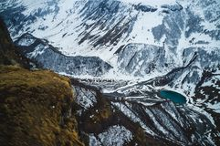 Panoramic view on the Kazbek mountains and the snow valley with a blue lake in Georgia. Panoramic view on the Kazbek mountains and the snow valley with a blue Royalty Free Stock Images