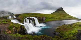 Panoramic view of Kirkjufellfoss and Kirkjufell mountain in cloudy day ,Iceland. stock photo
