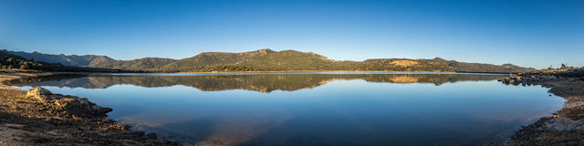 Panoramic view of lac de Codole in Balagne region of Corsica. Panoramic view at dawn across a mirror calm Lac de Codole at Regino in the Balagne region of Stock Images