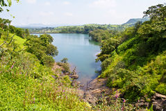Panoramic view of a lake flanked by greenery. Scenic and panoramic view of blue lake under blue skies, flanked by greenery on either sides Royalty Free Stock Photos