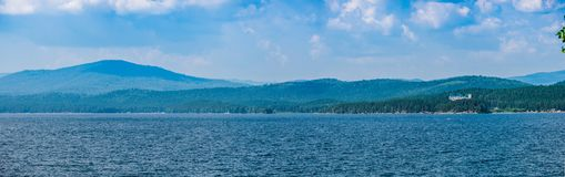 Panoramic view of the lake and forest with blue water and blue c stock images