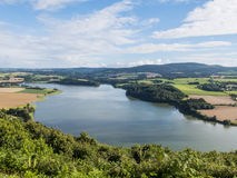 Panoramic view of Lake Huelgoat in Brittany, France. Around the. Lake you can see lush forests and cultivated fields. Blue sky with some clouds Royalty Free Stock Photos