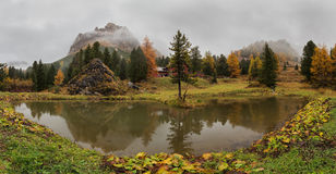Panoramic view of the lake and the mountain in the clouds. Dolomites. Stock Photos