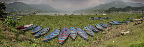Panoramic view of Lake Phewa with boats, Pokhara, Nepal. Panoramic view of Lake Phewa with boats and big montains in backgrounds, Pokhara, Nepal Royalty Free Stock Photography