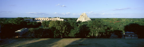 A panoramic view from left to right: Nunnery Quadrangle and the Pyramid of the Magician, Mayan ruin of Uxmal at sunset in the. Yucatan Peninsula, Mexico royalty free stock photos