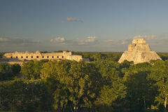 A panoramic view from left to right: Nunnery Quadrangle and the Pyramid of the Magician, Mayan ruin of Uxmal at sunset in the Yuca Stock Photo