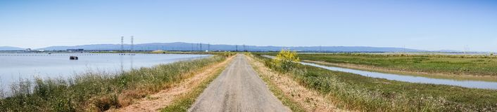 Panoramic view of levee going through the marsh and ponds in south San Francisco bay, California royalty free stock photography