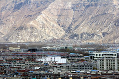 The panoramic view of Lhasa city, in front of Potala Palace and Palace square, with modern building and mountains, far away a Tib stock photography